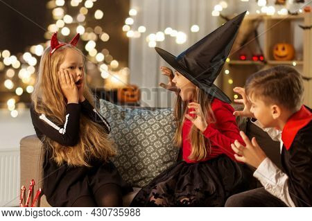 halloween, holiday and childhood concept - smiling boy and girls in party costumes playing and scaring each other at home at night