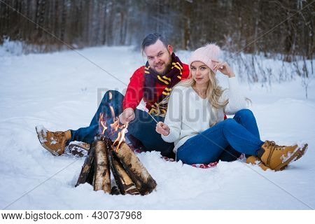 A Young Couple, An Adult Man And A Woman, Sit In The Snow Near A Campfire Outside In Winter. Young P