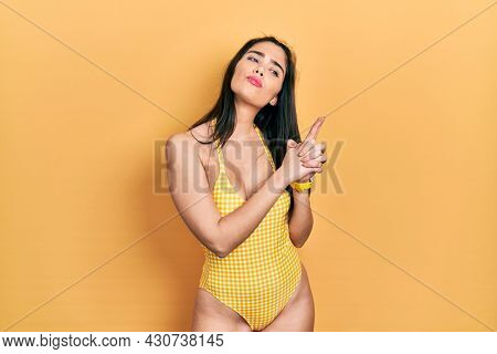 Young hispanic girl wearing swimsuit holding symbolic gun with hand gesture, playing killing shooting weapons, angry face