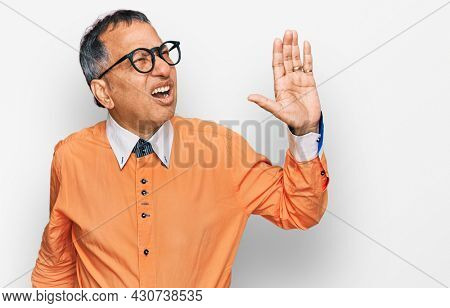 Middle age indian man wearing casual clothes and glasses shouting and screaming loud to side with hand on mouth. communication concept.