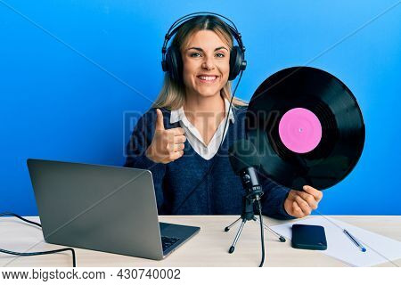 Young caucasian woman working at radio studio holding vinyl disc smiling happy and positive, thumb up doing excellent and approval sign