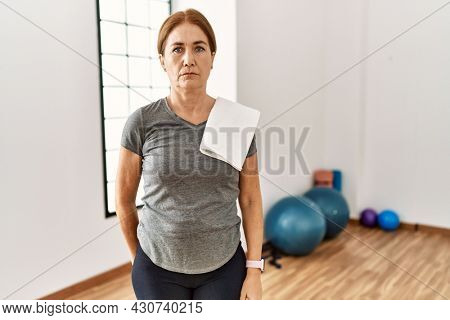 Middle age woman wearing sporty look training at the gym room relaxed with serious expression on face. simple and natural looking at the camera.