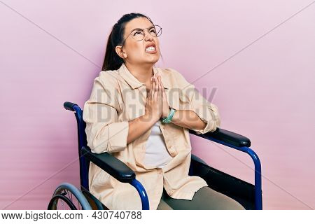 Young hispanic woman sitting on wheelchair begging and praying with hands together with hope expression on face very emotional and worried. begging.