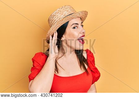 Young hispanic woman wearing summer hat smiling with hand over ear listening an hearing to rumor or gossip. deafness concept.
