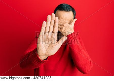 Middle age hispanic man wearing casual clothes and glasses covering eyes with hands and doing stop gesture with sad and fear expression. embarrassed and negative concept.