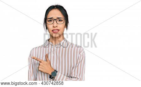 Young hispanic girl wearing casual clothes and glasses pointing aside worried and nervous with forefinger, concerned and surprised expression