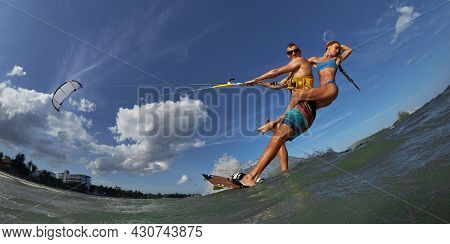 Lovely couple up on one kite board. Woman Riding On Kite surfer's Back and kiting on a sea