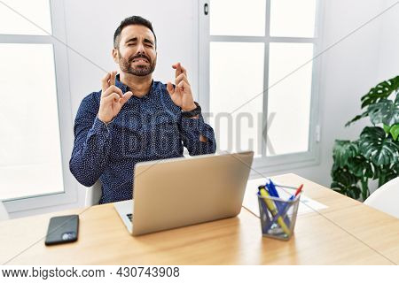 Young hispanic man with beard working at the office with laptop gesturing finger crossed smiling with hope and eyes closed. luck and superstitious concept.