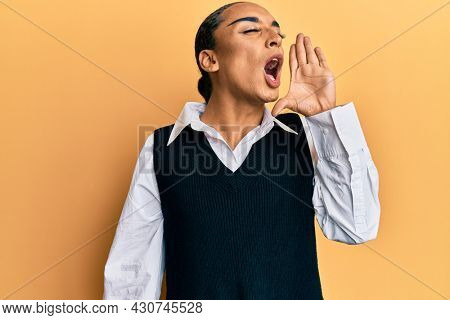 Hispanic man wearing make up and long hair wearing fashion clothes shouting and screaming loud to side with hand on mouth. communication concept.