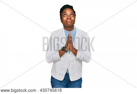 Young african american woman wearing business clothes begging and praying with hands together with hope expression on face very emotional and worried. begging.
