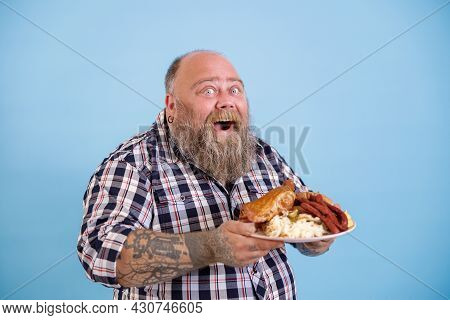 Happy Plump Man Holds Plate Of Fat Food Posing On Light Blue Background