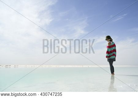 Asian Woman Standing In A Salt Lake Looking Down At The Water