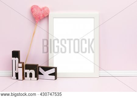 White picture frame, heart-shaped ornament and woodblock letters in front of pink wall. Feminine poster mockup. Blank image area masked with clipping path.