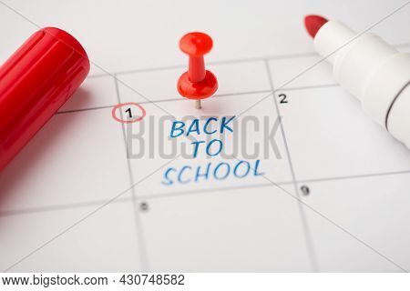 Closeup Photo Of Mark On Calendar At First Blue Inscription Back To School With Red Pushpin And Mark