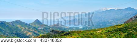 Panorama view of Crete island in Greece with green fields and wineries and flock of sheep grazing