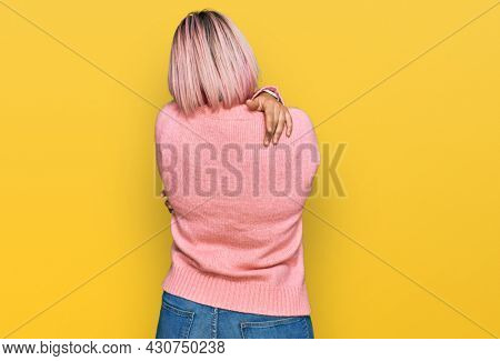 Hispanic woman with pink hair wearing casual winter sweater hugging oneself happy and positive from backwards. self love and self care