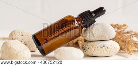 Side View Composition With Dark Glass Dropper Bottle Wit Essential Oil And Stones And Dry Reeds. Hom