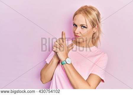 Young blonde woman wearing casual pink t shirt holding symbolic gun with hand gesture, playing killing shooting weapons, angry face