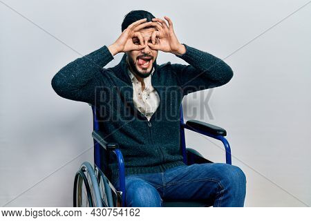 Handsome man with beard sitting on wheelchair doing ok gesture like binoculars sticking tongue out, eyes looking through fingers. crazy expression.