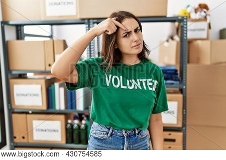 Young brunette woman wearing volunteer t shirt at donations stand pointing unhappy to pimple on forehead, ugly infection of blackhead. acne and skin problem
