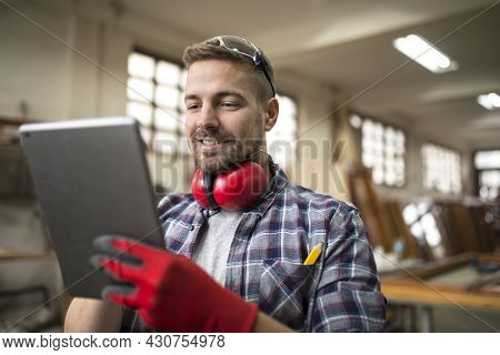 Portrait Of Middle Aged Professional Worker Carpenter With Ear Protectors Using Tablet In Carpentry
