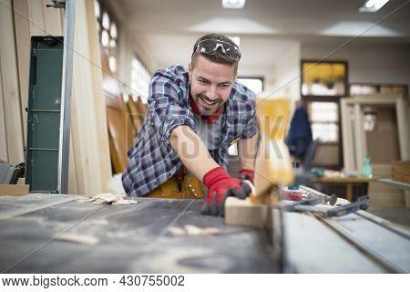 Professional Smiling Craftsman Cutting Plant On Circular Machine In Wood Working Carpentry Workshop.