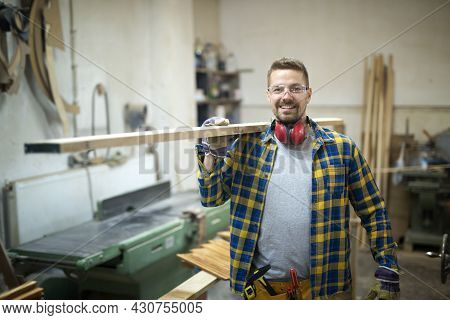 Professional Smiling Middle Aged Carpenter Holding Wood Plank In Woodworking Workshop.