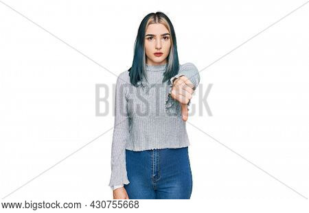 Young modern girl wearing casual sweater looking unhappy and angry showing rejection and negative with thumbs down gesture. bad expression.