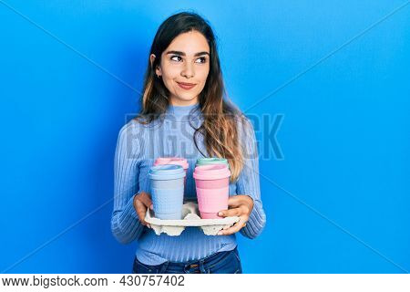 Young hispanic girl holding tray with take away coffee smiling looking to the side and staring away thinking.