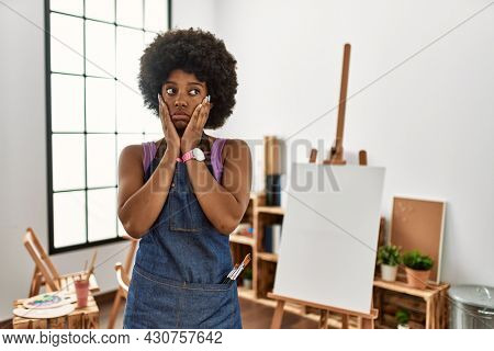 Young african american woman with afro hair at art studio tired hands covering face, depression and sadness, upset and irritated for problem