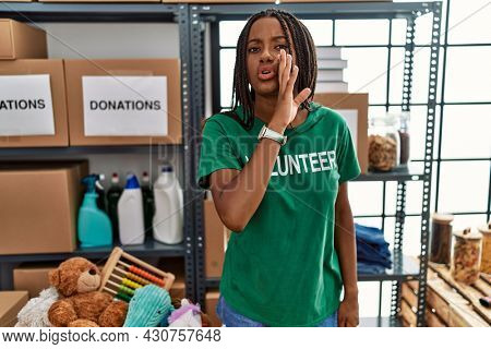 Young african american woman working wearing volunteer t shirt at donations stand hand on mouth telling secret rumor, whispering malicious talk conversation
