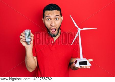 Hispanic man with beard holding solar windmill for renewable electricity and led bulb afraid and shocked with surprise and amazed expression, fear and excited face.
