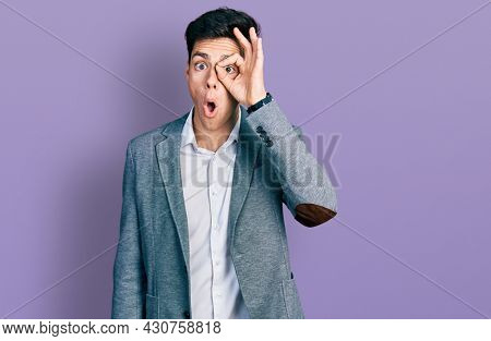 Young hispanic man wearing business clothes doing ok gesture shocked with surprised face, eye looking through fingers. unbelieving expression.