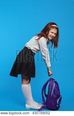 Full Size Body Schoolgirl In School Uniform Holding A Heavy Backpack, Isolated Against Blue Backgrou