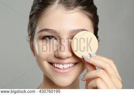 Beautiful Girl With Foundation Smear On Her Face Holding Sponge Against Grey Background, Closeup