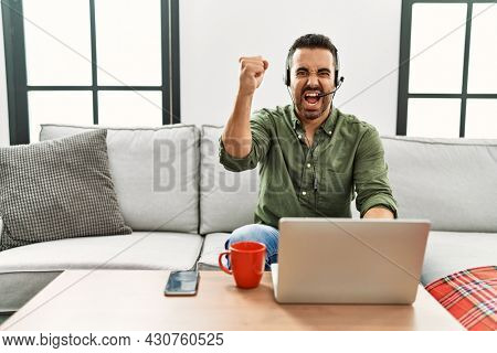 Young hispanic man with beard wearing call center agent headset working from home angry and mad raising fist frustrated and furious while shouting with anger. rage and aggressive concept.
