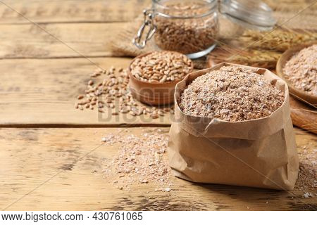 Paper Bag With Wheat Bran On Wooden Table, Space For Text