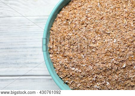 Bowl Of Wheat Bran On White Wooden Table, Top View