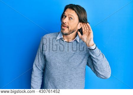 Middle age handsome man wearing casual clothes smiling with hand over ear listening and hearing to rumor or gossip. deafness concept.