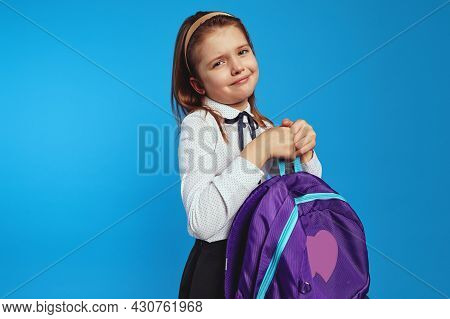 Schoolgirl In School Uniform Holding A Heavy Backpack, Isolated Against Blue Background. Problem Of