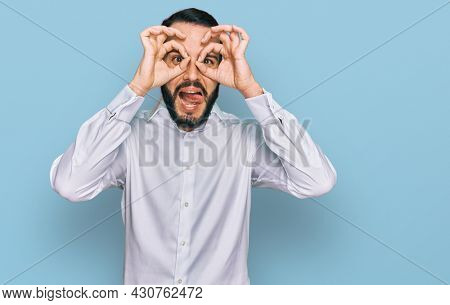 Young man with beard wearing business shirt doing ok gesture like binoculars sticking tongue out, eyes looking through fingers. crazy expression.