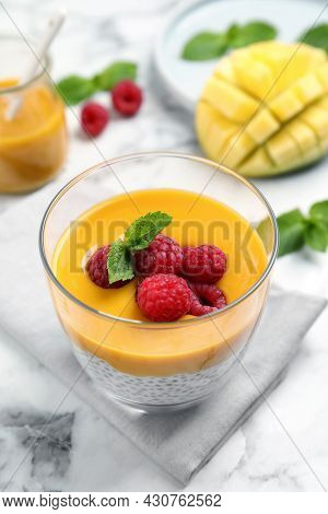 Delicious Chia Pudding With Mango Sauce And Raspberries On White Marble Table