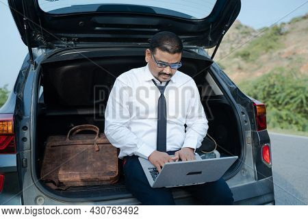 Young Businessman Working From The Car Trunk Or Boot Near Roadside - Concept Of Digital Nomadic Life