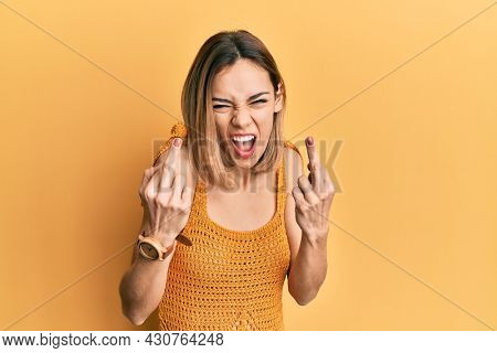 Young caucasian blonde woman wearing casual yellow t shirt showing middle finger doing fuck you bad expression, provocation and rude attitude. screaming excited