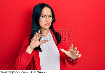 Beautiful hispanic woman with nose piercing wearing casual look and glasses disgusted expression, displeased and fearful doing disgust face because aversion reaction. with hands raised