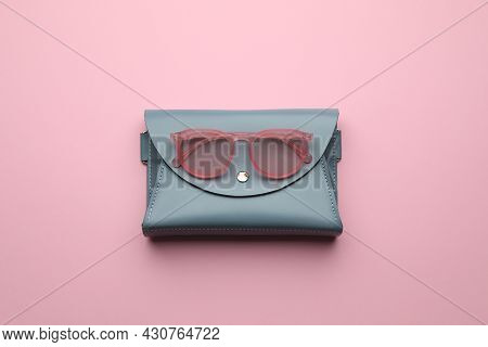 Stylish Woman's Bag And Sunglasses On Pink Background, Top View