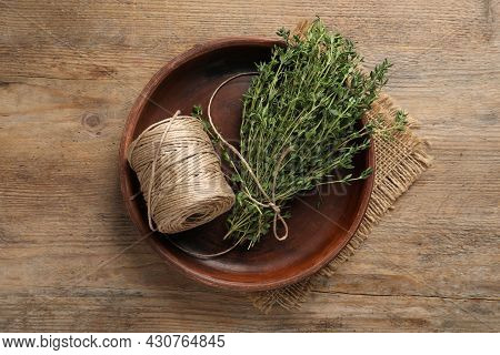 Bunch Of Aromatic Thyme And Twine In Bowl On Wooden Table, Top View