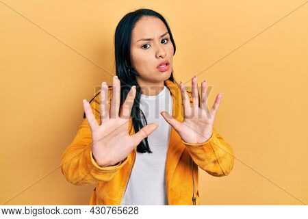Beautiful hispanic woman with nose piercing wearing yellow leather jacket moving away hands palms showing refusal and denial with afraid and disgusting expression. stop and forbidden.