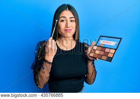 Young hispanic woman holding makeup brush and blush puffing cheeks with funny face. mouth inflated with air, catching air.