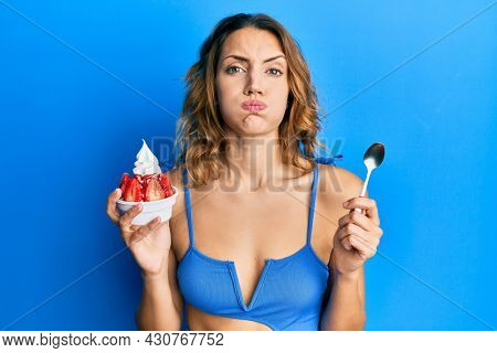 Young caucasian woman wearing bikini eating ice cream puffing cheeks with funny face. mouth inflated with air, catching air.
